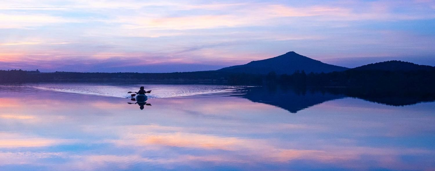 Welcome image of canoeists at sunset, paddling on a tranquil lake